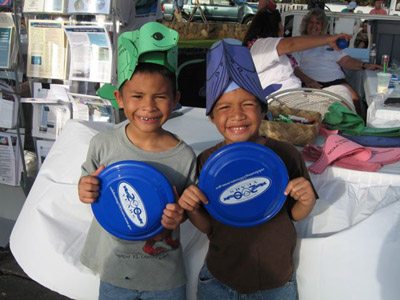 Two happy kids showing off their turtle and whale hats and new NOAA 200th Anniversary frisbees.