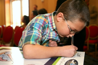 The First Grade Winner Signs His Artwork, Which Will Hang In His School